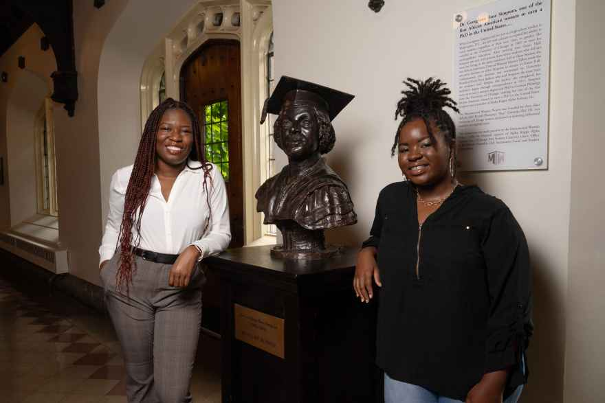 Third-year students Marla Anderson (right) and Dayo Adeoye pose with the bust of Georgiana Simpson in the Reynolds Club at the University of Chicago. Anderson and Adeoye created the Georgiana Simpson Organization last year to honor Simpson's pioneering legacy and foster the advancement of Black women at UChicago.