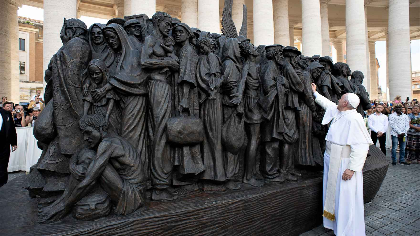 Pope Francis touches the Angels Unawares sculpture.